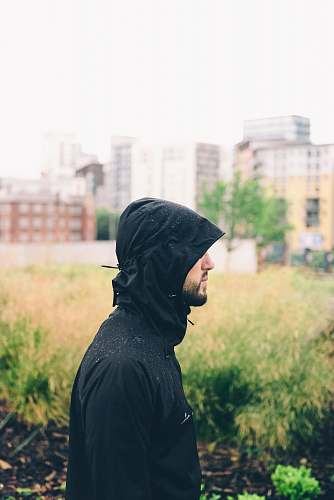 person man wearing hoodie standing near grass with building background during daytime manchester