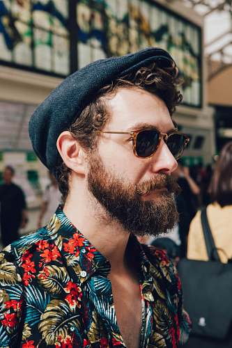 human man wearing multicolored floral shirt and black framed black lens sunglasses person