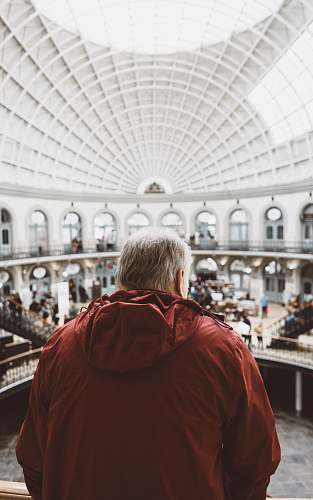 person man wearing red hoodie inside dome building in front of people human