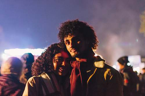 hair man wearing red scarf standing beside woman afro hairstyle