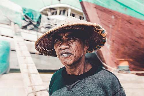 person man wearing straw hat near ships during day human