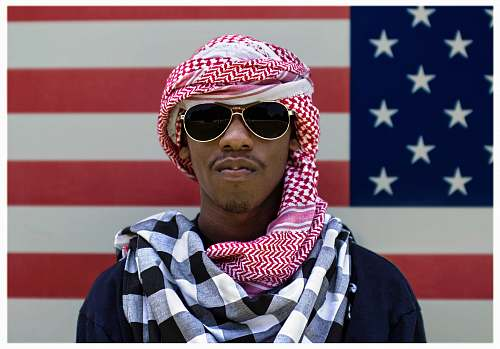human man wearing sunglasses in front of American flag person