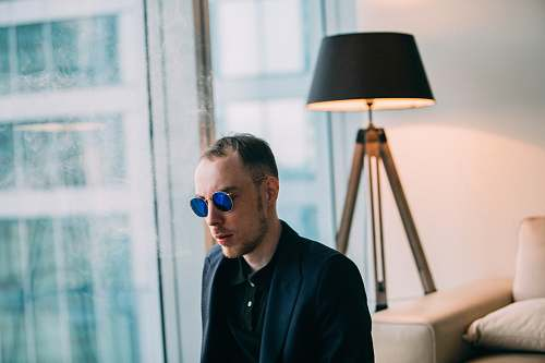 human man wearing sunglasses near table lamp photo person