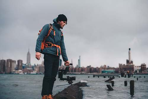 human man wearing teal zip-up bubble jacket taking photo of body of water with camera with stabilizer person
