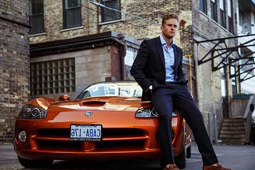 person men's black suit and orange coupe car