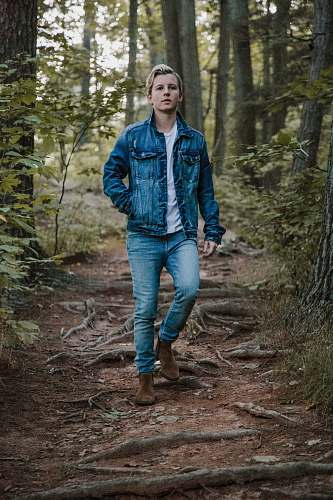 person men's blue denim button-up jacket between trees human