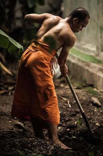 human monk gardening near grey wall person