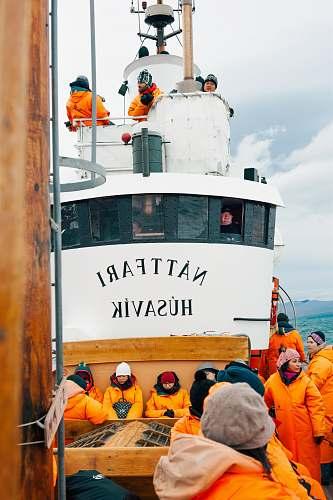 human people on white Nattfari Husavik ship on body of water during cloudy weather hat