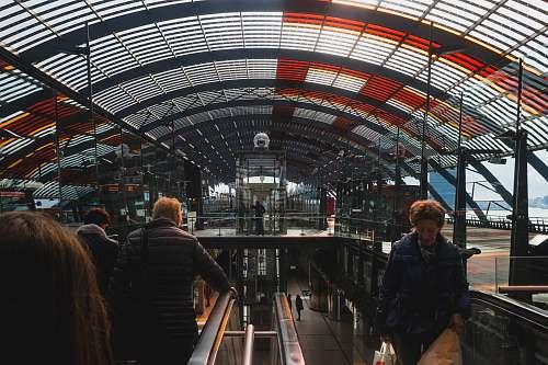 human people riding escalator inside building person