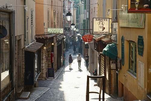 town people walking between buildings street