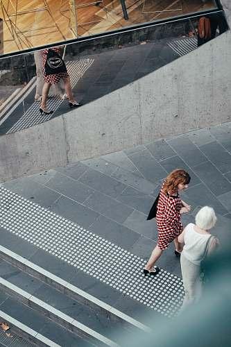 person people walking on street near mirrored wall human