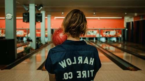 human person holding bowling ball facing bowling pins person