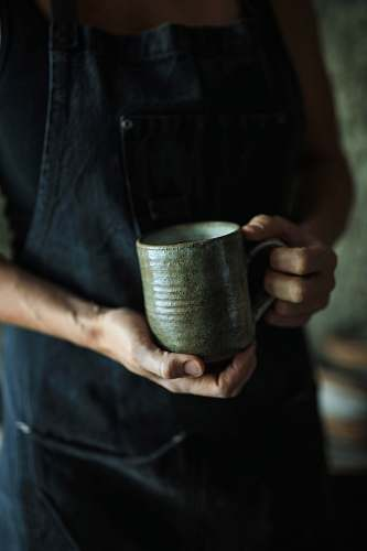 human person holding ceramic mug person