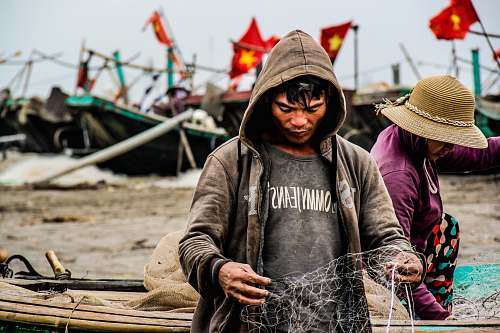 person person holding fishing net near brown boat during daytime human