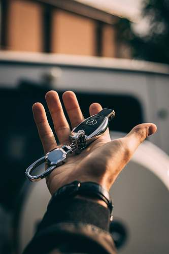 person person holding Mercedes-Benz fob human