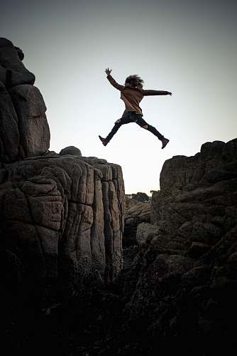 person person jumping on big rock under gray and white sky during daytime rock