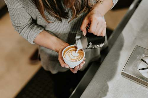 person person pouring cup of coffee in white ceramic cup human