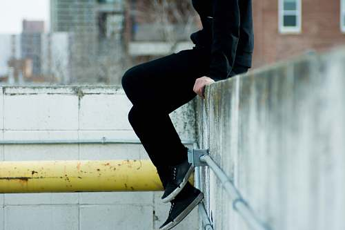 human person sitting on top of white concrete wall near yellow metal pipe person