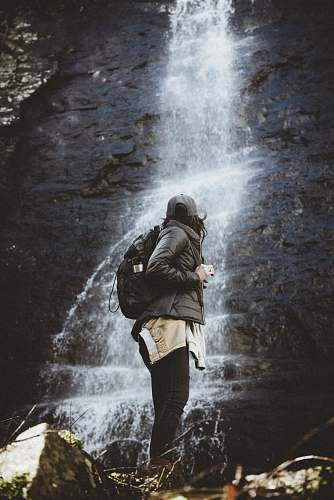 human person standing beside waterfalls person