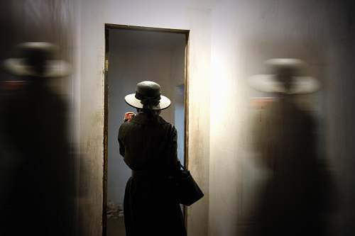 person person wearing hat carrying bag while standing in front of door hat