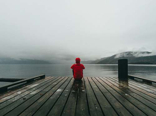 human person wearing red hooded jacket sitting on brown and black wooden sea dock near mountains under gray sky during daytime person