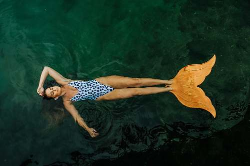 person photo of woman floating on body of water with mermaid tail flippers human