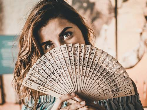 human photography of woman holding brown hand fan person