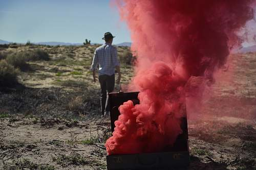 person red smoke bomb on chest near man wearing black cap smoke