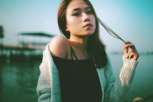 human selective focus photo of woman holding string of hair near body of water during daytime person