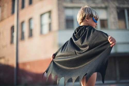 human selective focus photography of boy wearing black Batman cape person