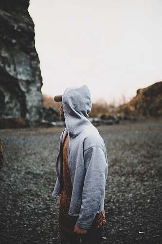 human selective focus photography of man standing near rock formation person