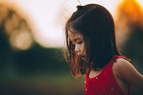 human selective focus photography of toddler wearing red tank top girl