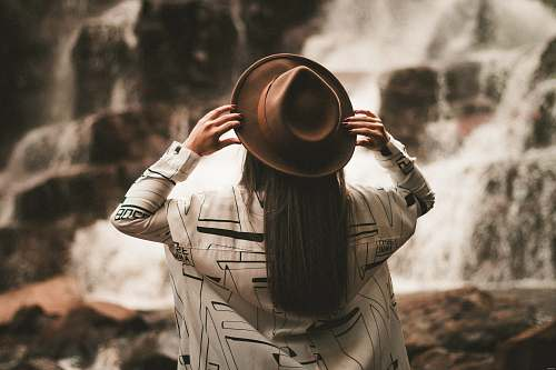 person selective focus photography of woman holding brown fedora hat at daytime human