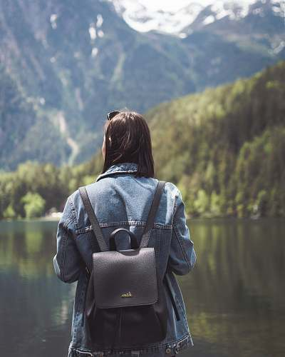 human selective focus photography of woman wearing blue denim jacket and black bucket backpack near lagoon at daytime person
