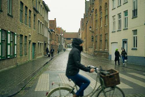 human selective photography of people walking on sidewalks at side of buildings view from person riding city bicycle person