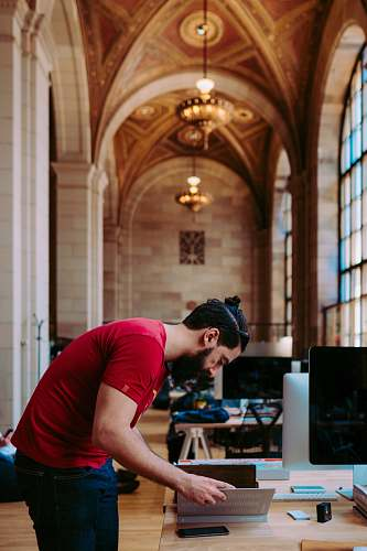 person shallow focus photogoraphy of man looking down to his book monitor