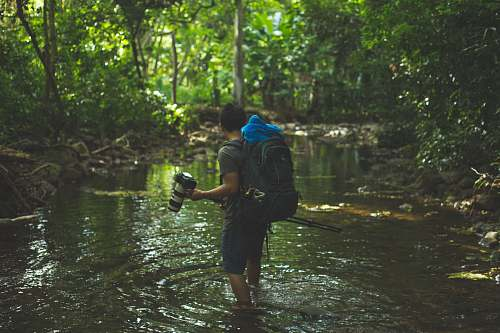 human shallow focus photography of man walking in river person