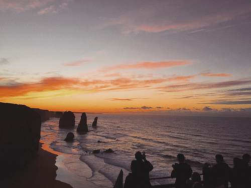 person silhouette of people standing near 12 Apostles landmark in Australia human