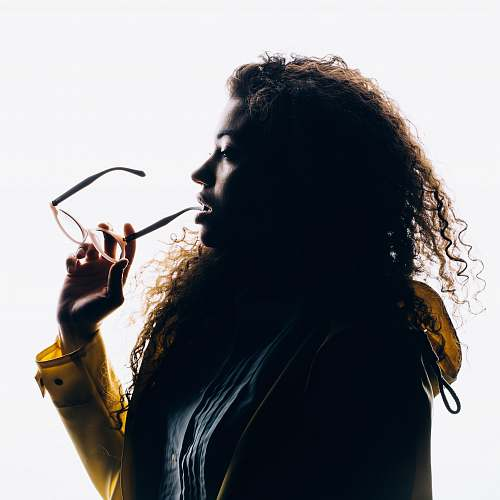 human silhouette photo of woman biting her eyeglasses person