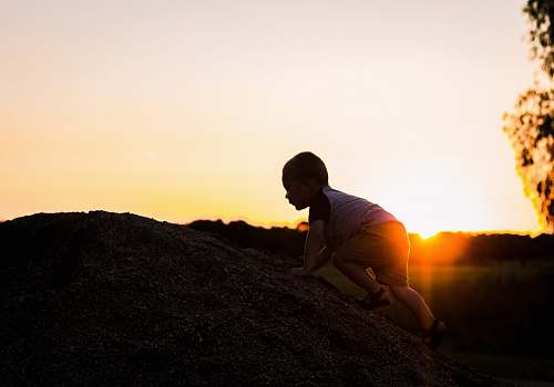 human silhouette photography of child climbing on rock person