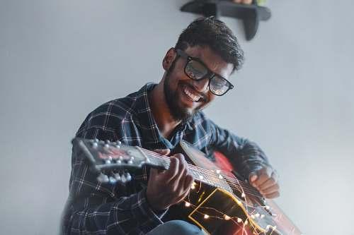 human smiling man sitting while playing guitar person