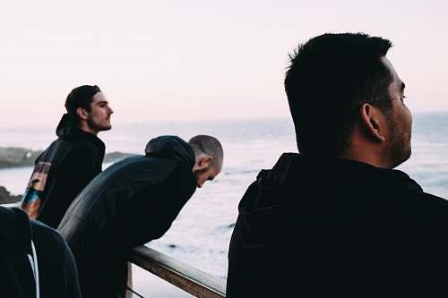 person three men near rail near sea human