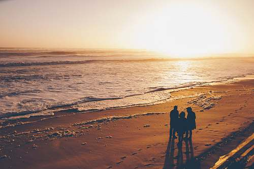 beach three people standing on sand near ocean during golden hour coast