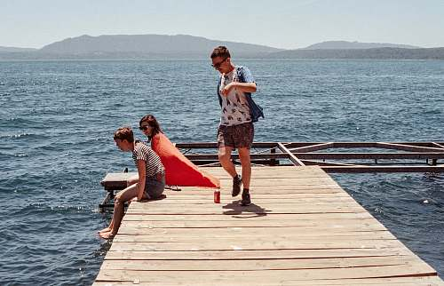 person three person standing on dock pier