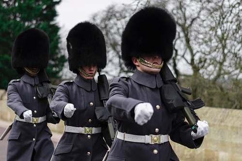 human three Queen's guards carrying sub-machine guns person