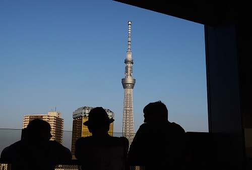 person three silhouette of persons standing in front window watching tower building human