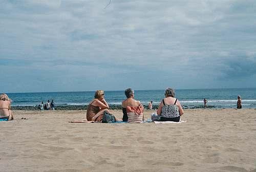 beach three women sitting on beach sea