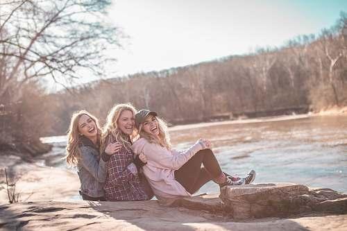 woman three women sitting on rock near body of water blonde