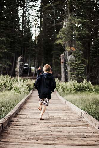 person toddler running on brown wooden pathway human