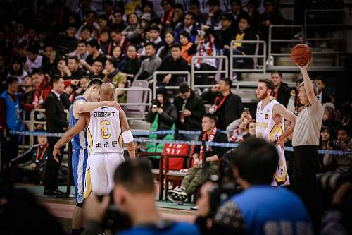 human two basketball players about to hug each other at the court person